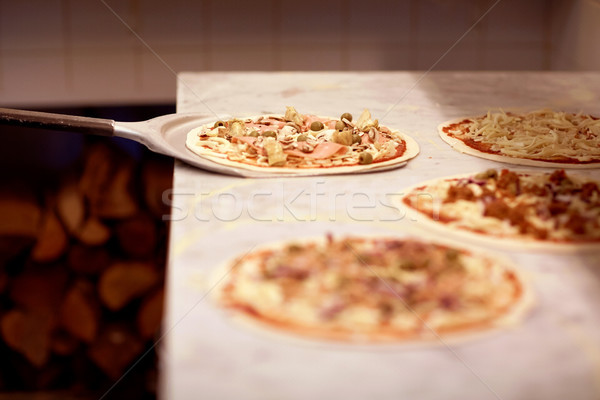 peel taking pizza off table at pizzeria Stock photo © dolgachov