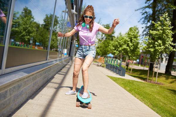 happy teenage girl in shades riding on longboard Stock photo © dolgachov