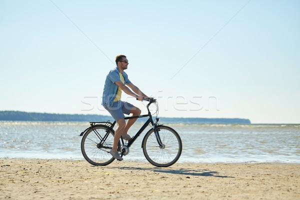 happy man riding bicycle along summer beach Stock photo © dolgachov