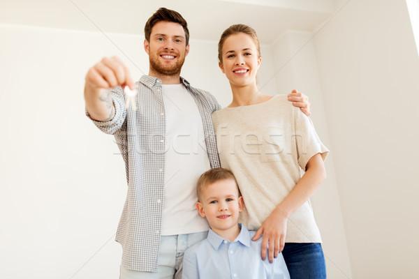 happy family with key moving to new home Stock photo © dolgachov