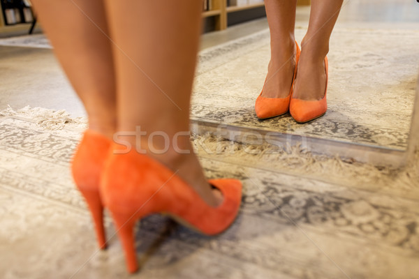 legs of woman in high-heeled shoes at store mirror Stock photo © dolgachov