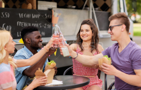friends clinking drinks and eating at food truck Stock photo © dolgachov