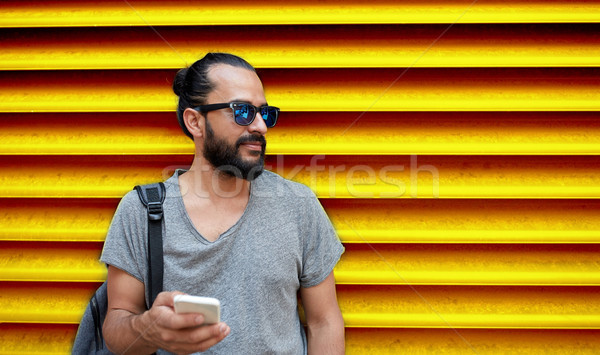 man in sunglasses with smartphone and bag at wall Stock photo © dolgachov