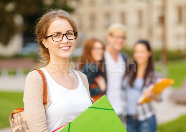 Stock photo: female student in eyglasses with folders