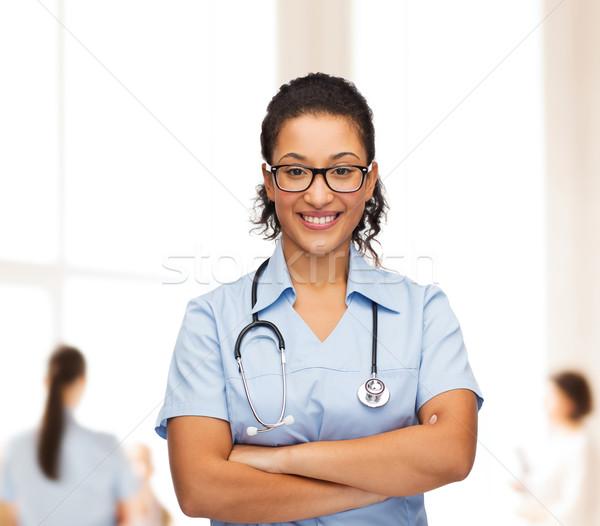smiling female african american doctor or nurse Stock photo © dolgachov