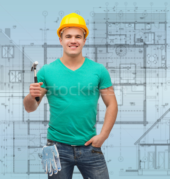smiling manual worker in helmet with hammer Stock photo © dolgachov