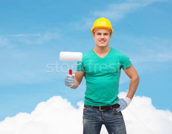 smiling manual worker in helmet with paint roller Stock photo © dolgachov
