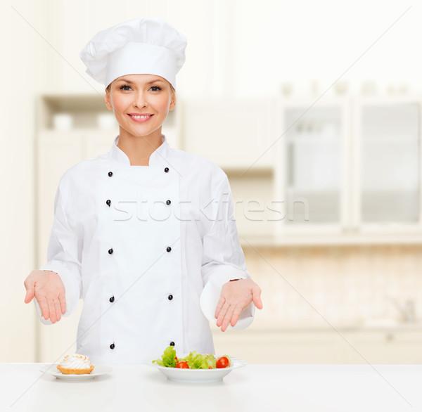 smiling female chef with salad and cake on plates Stock photo © dolgachov