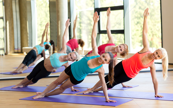 smiling women meditating on mat in gym Stock photo © dolgachov
