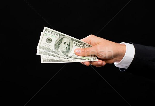 close up of male hand holding dollar cash money Stock photo © dolgachov