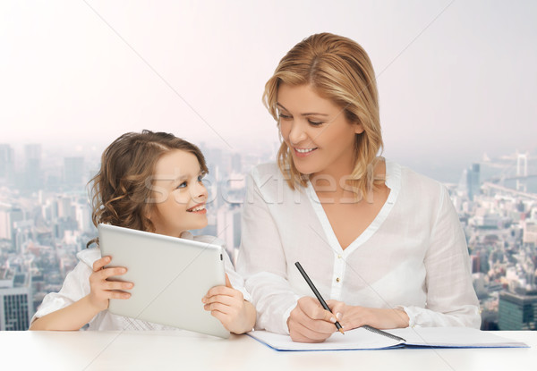 woman with notebook and girl holding tablet pc  Stock photo © dolgachov
