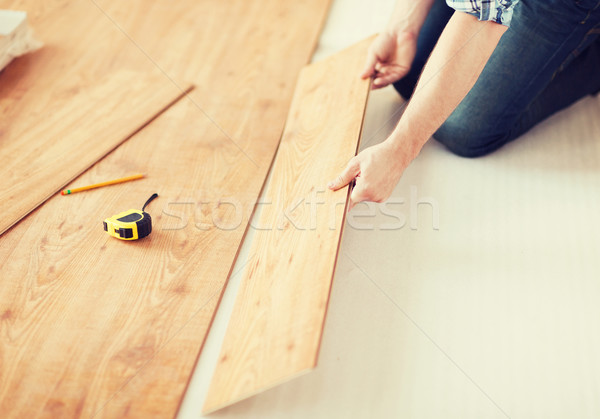 Stock photo: close up of male hands intalling wood flooring