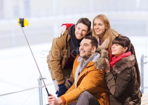 happy friends with smartphone on skating rink Stock photo © dolgachov