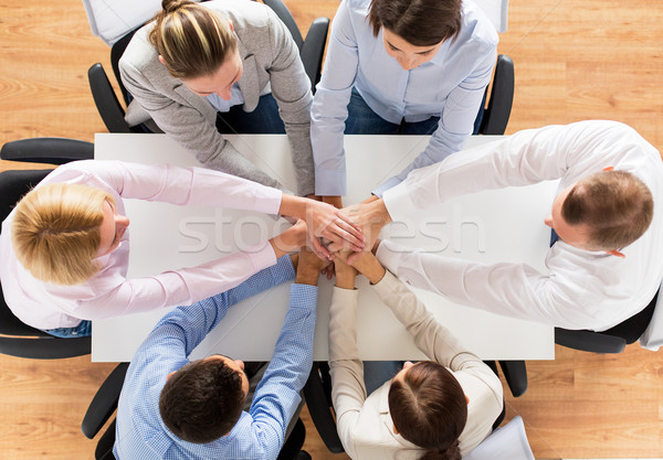 close up of business team with hands on top Stock photo © dolgachov