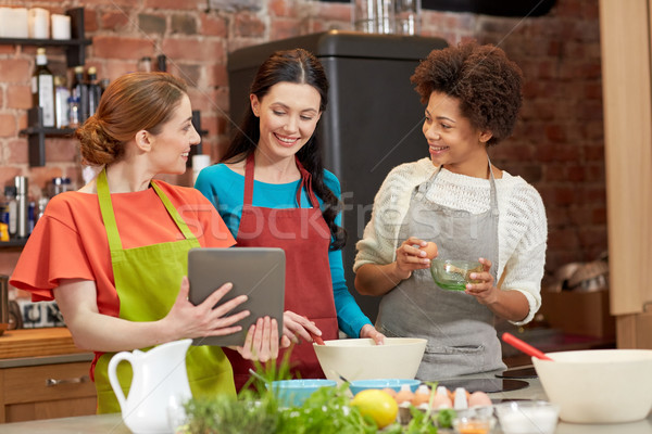 happy women with tablet pc cooking in kitchen Stock photo © dolgachov