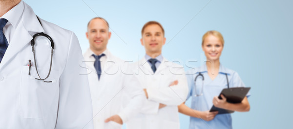 group of happy medics in white coats Stock photo © dolgachov