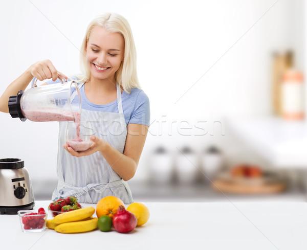 Glimlachende vrouw vruchten milkshake gezond eten koken Stockfoto © dolgachov