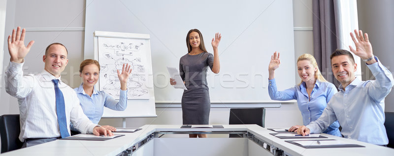 group of businesspeople waving hands in office Stock photo © dolgachov