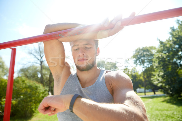 man with heart-rate watch exercising outdoors Stock photo © dolgachov