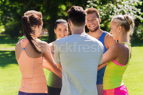 group of happy friends with hands on top outdoors Stock photo © dolgachov