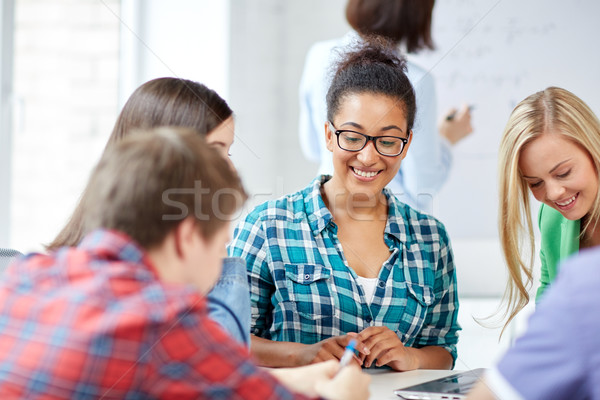 group of happy high school students with workbook Stock photo © dolgachov