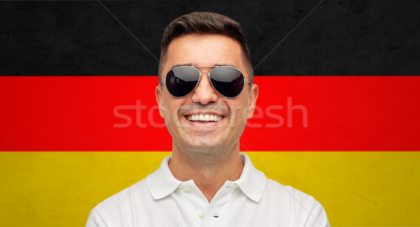 face of smiling man in sunglasses over german flag Stock photo © dolgachov