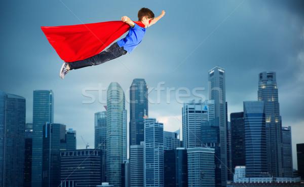boy in red superhero cape flying over city Stock photo © dolgachov