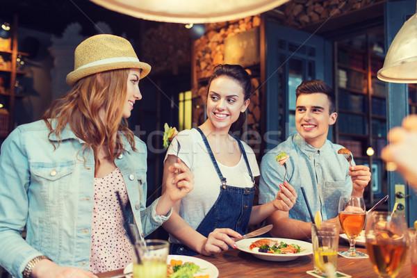 Felice amici mangiare bere bar pub Foto d'archivio © dolgachov