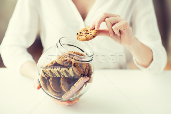 close up of hands with chocolate cookies in jar Stock photo © dolgachov