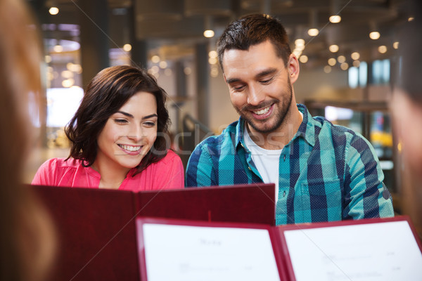 smiling couple with friends and menu at restaurant Stock photo © dolgachov