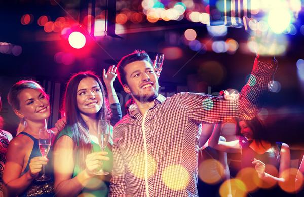 friends taking selfie by smartphone in night club Stock photo © dolgachov
