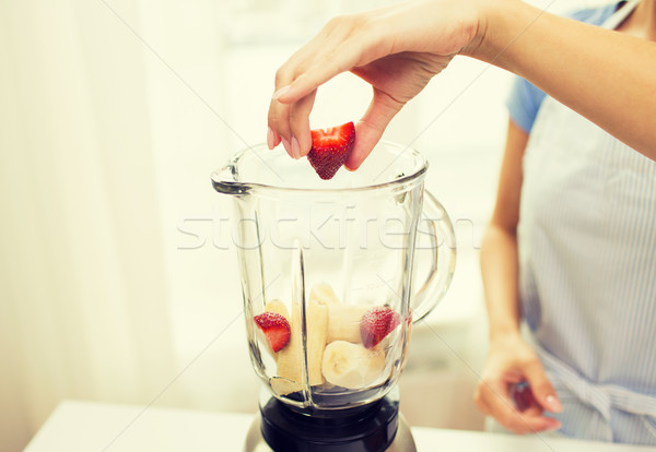 Stock photo: close up of woman with blender making fruit shake