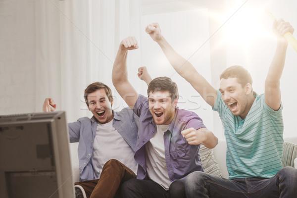 happy male friends with vuvuzela watching sports Stock photo © dolgachov