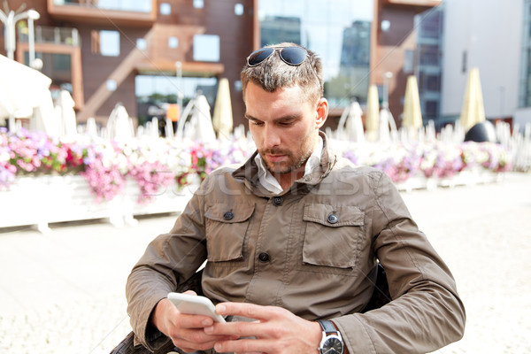 young man texting on smartphone at city terrace Stock photo © dolgachov
