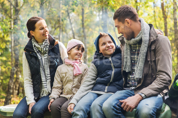happy family sitting on bench and talking at camp Stock photo © dolgachov