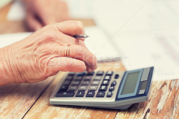 close up of senior woman counting with calculator Stock photo © dolgachov
