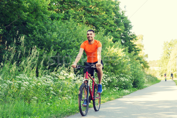 happy young man riding bicycle outdoors Stock photo © dolgachov