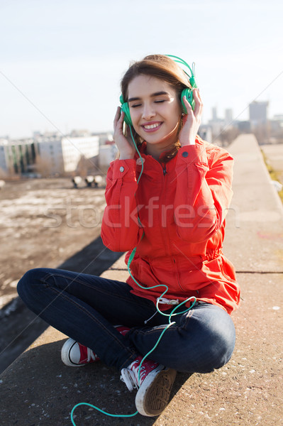 happy young woman in headphones listening to music Stock photo © dolgachov