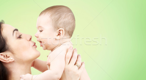 Stock photo: happy mother kissing adorable baby