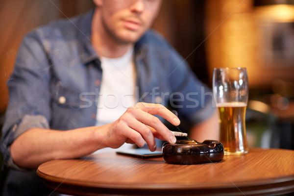 Férfi iszik sör dohányzás cigaretta bár Stock fotó © dolgachov