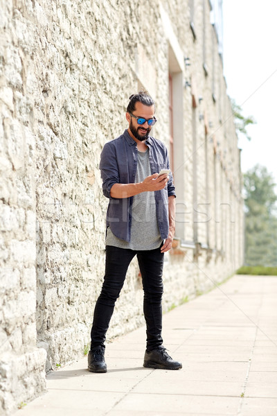 man texting message with smartphone on city street Stock photo © dolgachov
