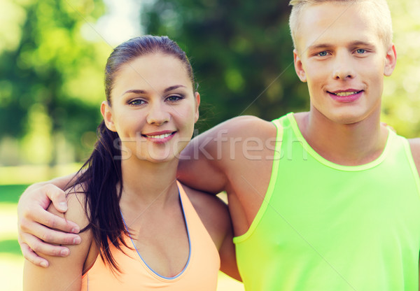 happy friends or sportsmen couple hugging outdoors Stock photo © dolgachov