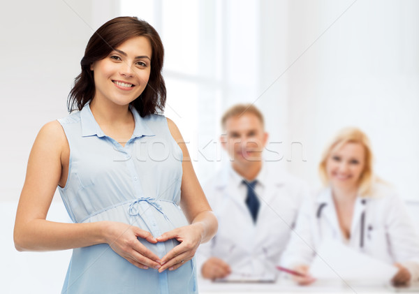 Stock photo: happy pregnant woman making heart gesture on belly