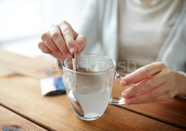 woman stirring medication in cup of water Stock photo © dolgachov