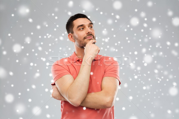 man in polo t-shirt thinking over snow background Stock photo © dolgachov