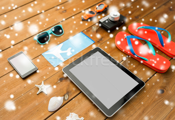 tablet pc, airplane ticket and beach stuff Stock photo © dolgachov