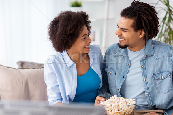 Souriant couple popcorn regarder tv maison Photo stock © dolgachov