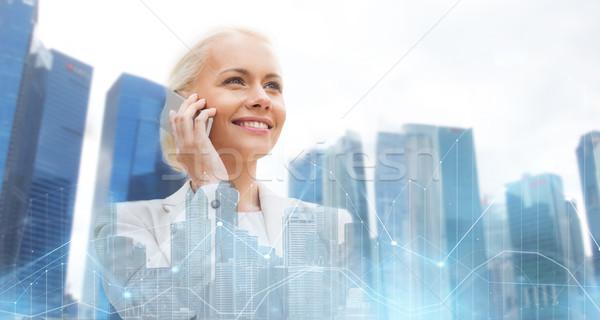 happy businesswoman calling on smartphone in city Stock photo © dolgachov