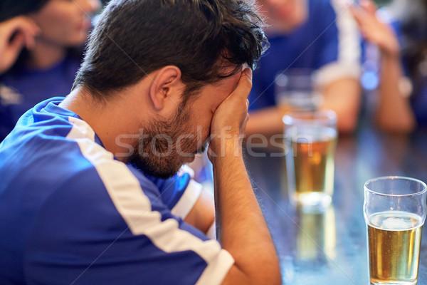 close up of sad football fan at bar or pub Stock photo © dolgachov
