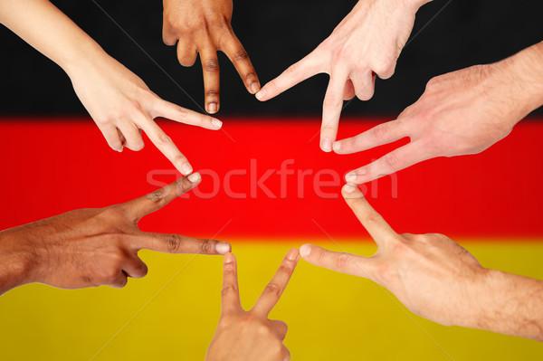 Groep internationale mensen tonen vrede teken Stockfoto © dolgachov